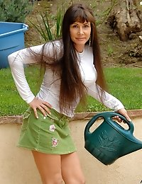 Housewife Alexandra Silk bends over in her miniskirt while watering the flowers